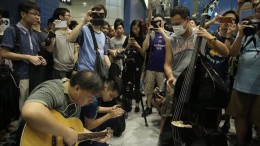 Music lovers play music at MTR station to vent out their anger over baggage rules.