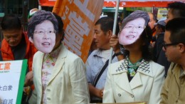 Chief Secretary Carrie Lam is ridiculed by protesters for failing to meet their demands for universal retirement protection.