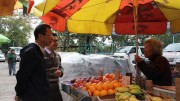 Legislative Council President Tsang Yok-sing talks to fruit stall owner at Wah Fu Estate. He dismisses fears that universal suffrage would result in welfarism.