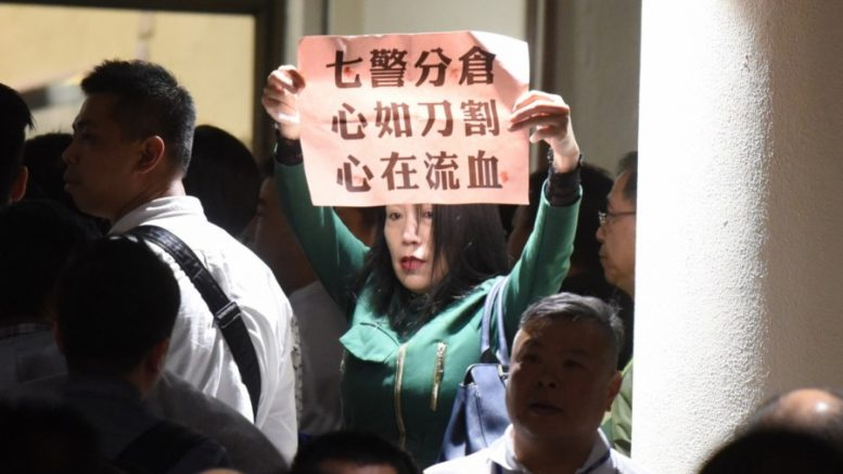 A woman lends her support to the seven police officers convicted of assaulting an activist during the Occupy Central movement at a rally on Wednesday.