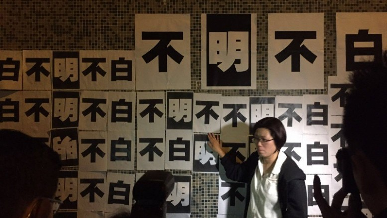 """Ming Pao staff post paper bills on the wall of the newspaper group's building in Chai Wan Wednesday night , saying they """"don't understand"""" the management's decision to sack a top editor on the ground of cost-cutting."""