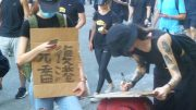 Young protesters pen slogan, 'Liberate Hong Kong, revolution of our times' at rally.