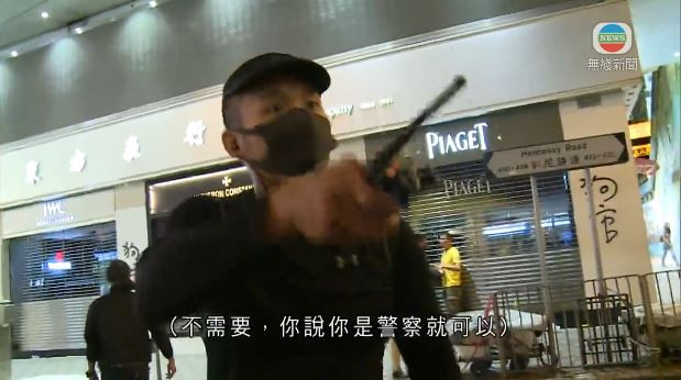 Dressed in black like protester, an identified man believed to be undercover police confronts journalists after making arrests in the August 11 clash.